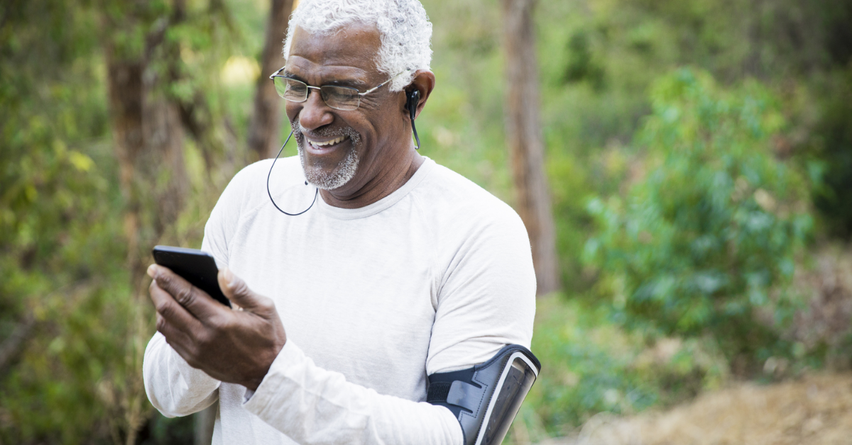 older man walking in woods looking at phone